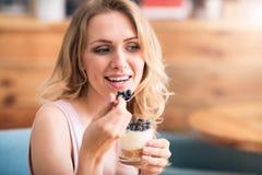 Mujer joven agradable que come el desierto Foto de archivo libre de regalías