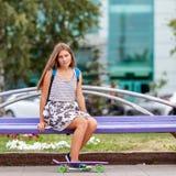 Mujer joven agradable y de la moda que presenta con el monopatín Foto de archivo