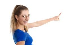 Mujer joven aislada en la camisa azul que presenta con su finger encendido Fotos de archivo