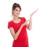 Mujer joven aislada que presenta en una camisa roja. Fotografía de archivo libre de regalías