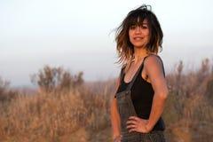 Mujer joven al aire libre en guardapolvos en la puesta del sol Fotos de archivo libres de regalías