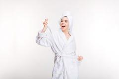 Mujer joven alegre alegre en albornoz con la toalla en la cabeza Imágenes de archivo libres de regalías