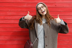 Mujer joven alegre alegre que se levanta y que muestra los pulgares Fotos de archivo