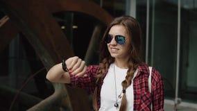 Mujer joven alegre con el pelo trenzado marrón y la ropa moderna del vidrio y casual que miran su reloj fresco cerca almacen de video