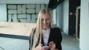 Mujer joven alegre con el teléfono en oficina Mujer bastante rubia con el pelo largo que lleva el traje negro elegante y la sonri almacen de metraje de vídeo