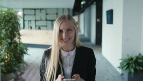 Mujer joven alegre con el teléfono en oficina Mujer bastante rubia con el pelo largo que lleva el traje negro elegante y la sonri almacen de video