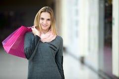 Mujer joven alegre con las bolsas de papel en centro comercial Imagenes de archivo