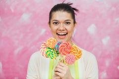 Mujer joven alegre con las piruletas coloridas sobre backgroun rosado Fotografía de archivo libre de regalías