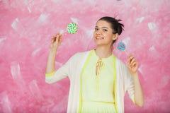Mujer joven alegre con las piruletas coloridas sobre backgroun rosado Fotos de archivo libres de regalías