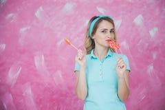 Mujer joven alegre con las piruletas coloridas sobre fondo rosado Imagenes de archivo
