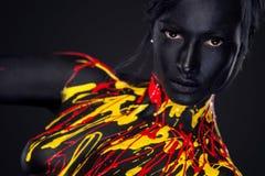 Mujer joven alegre con maquillaje de la moda del arte Una mujer asombrosa con maquillaje negro, amarillo y rojo de la pintura fotografía de archivo libre de regalías