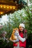 Mujer joven alegre con un animal doméstico en el bazar de la Navidad Imágenes de archivo libres de regalías