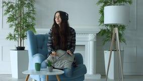 Mujer joven alegre en auriculares que disfruta de música metrajes