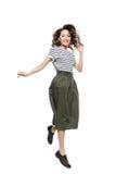 Mujer joven alegre en camiseta rayada y la falda que saltan y que sonríen en la cámara fotos de archivo libres de regalías
