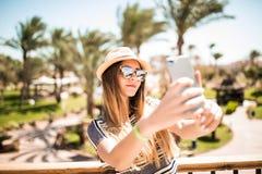 Mujer joven alegre en el sombrero y las gafas de sol que toman el selfie con el teléfono móvil en centro turístico de verano Voca Imagen de archivo libre de regalías