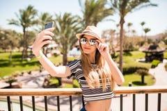 Mujer joven alegre en el sombrero y las gafas de sol que toman el selfie con el teléfono móvil en fondo de las palmas del centro  Foto de archivo