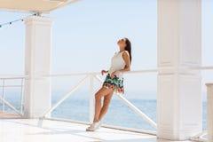 Mujer joven alegre en la camisa blanca que presenta en la cámara al aire libre Fotografía de archivo