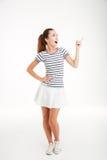 Mujer joven alegre en la falda que coloca y que señala el finger lejos Imagen de archivo libre de regalías