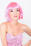 Mujer joven alegre en la peluca rosada que presenta en el fondo blanco Foto de archivo