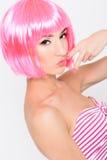 Mujer joven alegre en la peluca rosada que presenta en el fondo blanco Imagen de archivo libre de regalías