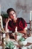 Mujer joven alegre en libro de lectura viejo del vestido de la moda en el restaurante adornado para la Navidad Para fecha que esp Imagenes de archivo