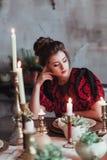 Mujer joven alegre en libro de lectura viejo del vestido de la moda en el restaurante adornado para la Navidad Para fecha que esp Fotos de archivo