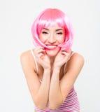 Mujer joven alegre en peluca rosada y presentación en el fondo blanco Foto de archivo libre de regalías