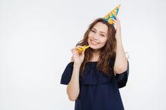Mujer joven alegre en sombrero del cumpleaños con el silbido del partido Imagenes de archivo