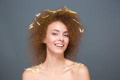 Mujer joven alegre feliz con los pétalos en el pelo y los hombros Foto de archivo