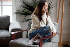 Mujer joven alegre feliz que habla en el teléfono en casa imagenes de archivo