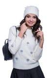 Mujer joven alegre hermosa que lleva el suéter, el sombrero y la mochila hechos punto Aislado en el fondo blanco Ella está sonrie Imagen de archivo libre de regalías