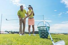 Mujer joven alegre que aprende el apretón y el movimiento correctos para usar al club de golf Fotografía de archivo libre de regalías