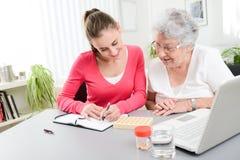 Mujer joven alegre que ayuda a una mujer mayor con la prescripción médica de las píldoras Imagen de archivo libre de regalías