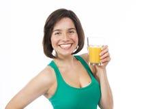 Mujer joven alegre que bebe un zumo de naranja Imágenes de archivo libres de regalías