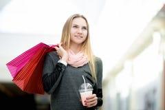 Mujer joven alegre que camina en centro comercial con las bolsas de papel Foto de archivo libre de regalías