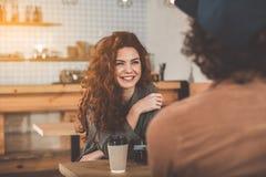 Mujer joven alegre que charla con el hombre dentro Fotos de archivo libres de regalías
