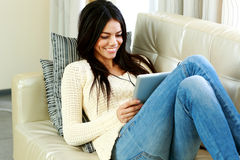 Mujer joven alegre que descansa sobre un sofá con la tableta Imagenes de archivo