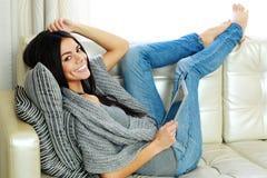 Mujer joven alegre que descansa sobre un sofá con la tableta Fotos de archivo libres de regalías