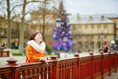 Mujer joven alegre que disfruta de la estación de la Navidad en París Imagen de archivo libre de regalías