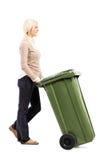 Mujer joven alegre que empuja un cubo de la basura Fotos de archivo