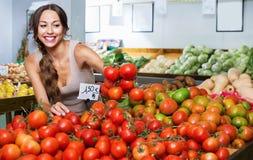 Mujer joven alegre que escoge los tomates frescos imagenes de archivo
