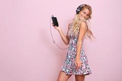 Mujer joven alegre que escucha la música Imágenes de archivo libres de regalías