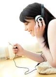 Mujer joven alegre que escucha la música en el suelo Imágenes de archivo libres de regalías