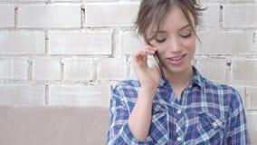 Mujer joven alegre que habla en el teléfono móvil en casa metrajes