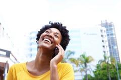 Mujer joven alegre que habla en el teléfono móvil en la ciudad Fotos de archivo