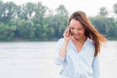 Mujer joven alegre que habla en el teléfono y que ríe en alta voz en el riverbank Tecnología moderna, viaje, forma de vida imagen de archivo