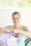 Mujer joven alegre que hace el lavadero Imágenes de archivo libres de regalías