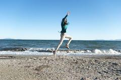 Mujer joven alegre que juega en la playa Fotografía de archivo