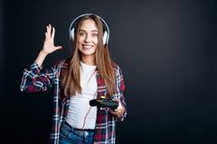 Mujer joven alegre que juega a los videojuegos Foto de archivo