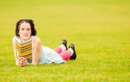 Mujer joven alegre que lee un libro exterior y relajante Imagen de archivo libre de regalías